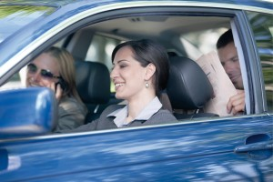 Woman driving car with two other people